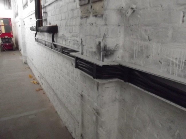 Isolierte Starkstromkabel, die an der Wand verlaufen